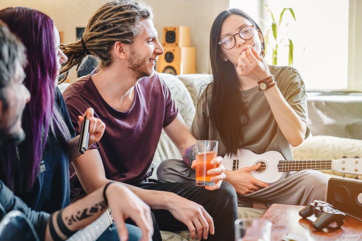 4 young adults smoking, drinking, playing music